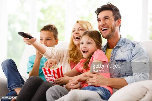 Family watching TV and eating popcorn