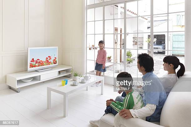 A family watching TV in the living room.