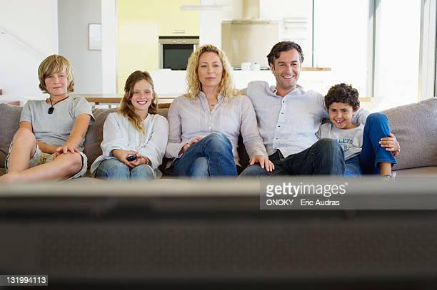 Family watching TV together at home