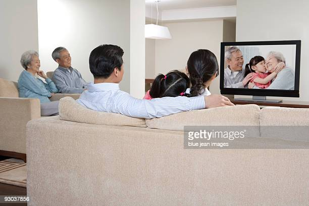 Family watching widescreen televisioin