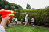 Point of view shot of a man having a water fight with water pistols in the garden with his wife and son.