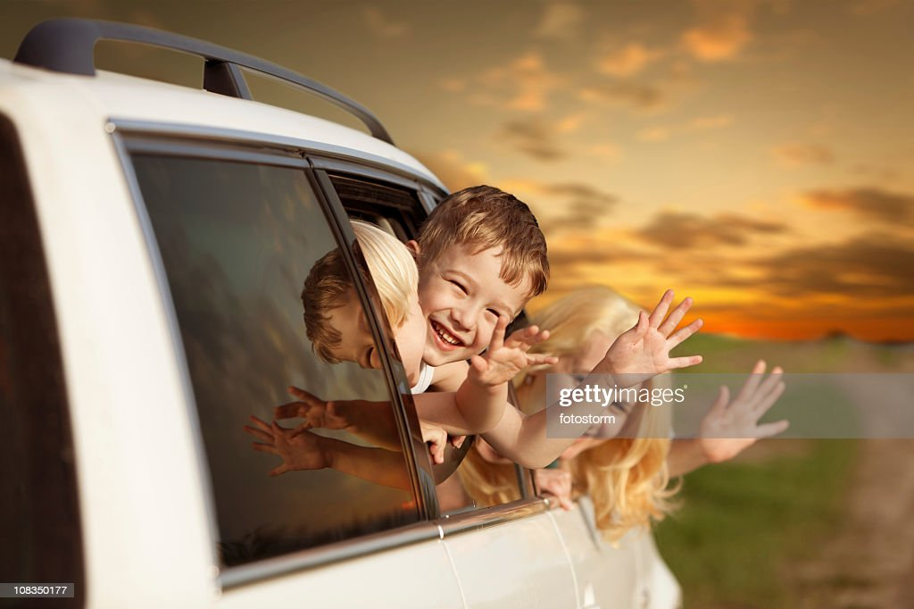 Family waving from car and traveling for a vacation : Stock Photo