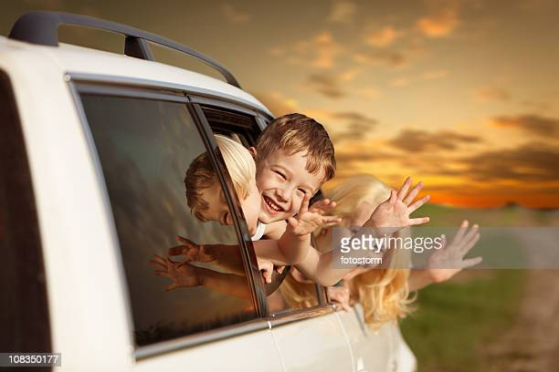 Family waving from car and traveling for a vacation