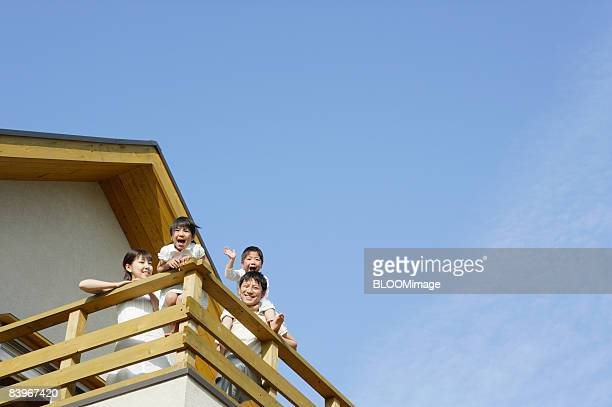 Family waving on balcony