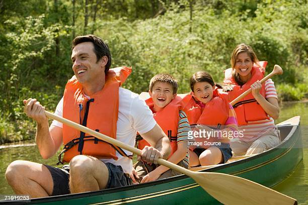 Family wearing life jacket in canoe
