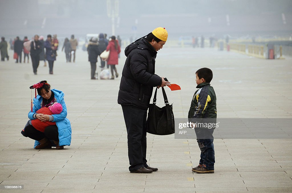 A family wearing Qing dynasty style headwear stand in Tiananmen square in Beijing on December 20, 2012. China said on December 18 it faces a bleak foreign trade environment in 2013 due to ongoing global economic weakness, as the Asian export powerhouse appears set to miss this year's trade growth target. AFP PHOTO / WANG ZHAO