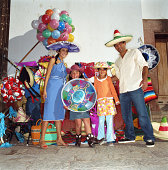 Family wearing sombrero  in front of market, smiling, portrait