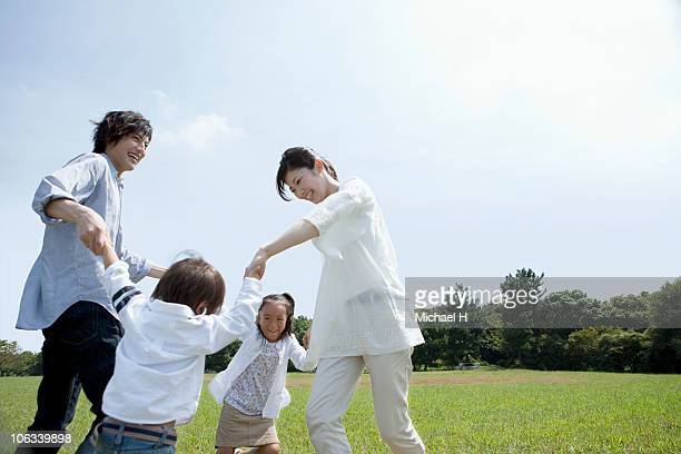 Family who becomes circle in park and plays