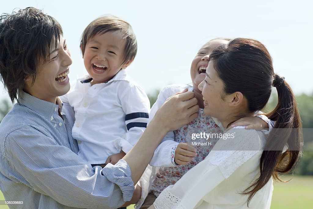 Family who happily with a smile in park : Stock Photo