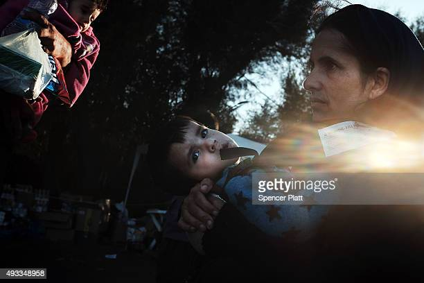 A family who just arrived from on a raft from Turkey pauses at a refugee reception center on the island of Lesbos on October 19 2015 in Sikaminias...