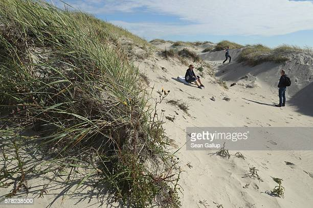 A family who said they did not mind being photographed relax at a dune near the beach on July 18 2016 at SanktPeterOrding Germany SanktPeterOrding is...