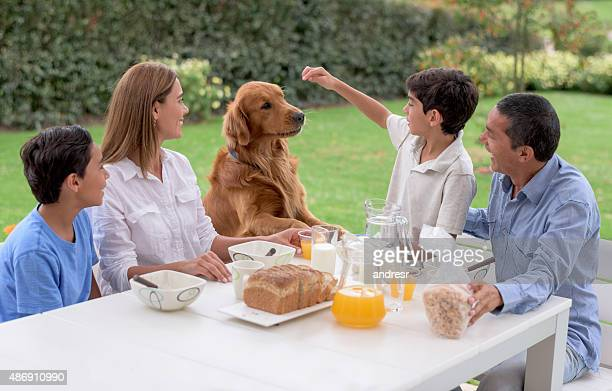 Family with a dog having breakfast in the morning