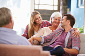 Family With Adult Children Relaxing On Sofa At Home Together, Smiling