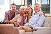 Family With Adult Children Relaxing On Sofa At Home Together, Smiling To Camera