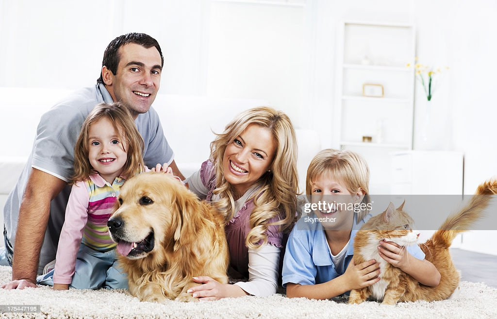 Family with animals sitting on the carpet : Stock Photo