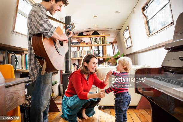 Family with baby boy living on barge playing guitar and dancing