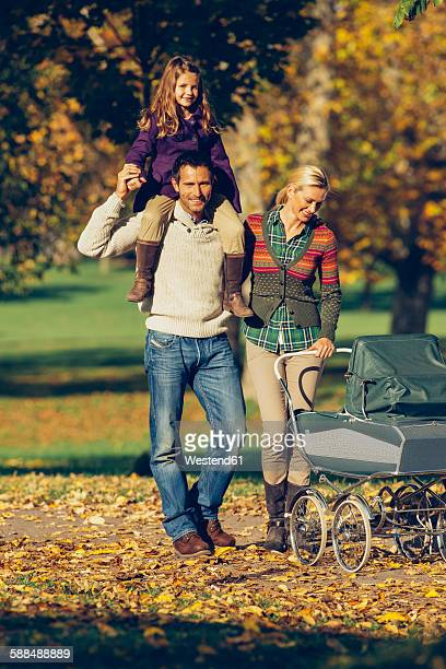 Family with baby carriage enjoying walk at the autumnal park