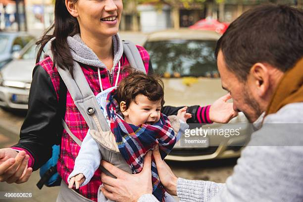 Family With Baby Son In Carrier Walking Through the city