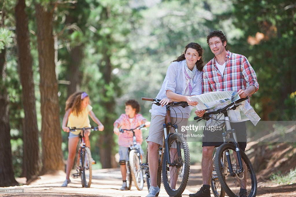 Family with bicycles looking at map in woods : Stock Photo