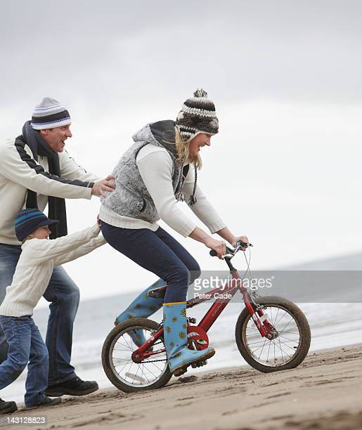 family with bike on beach in winter