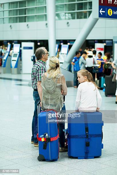 Family with blue suitcases at airport