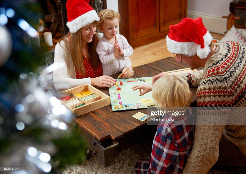 Family with board game, parents in Christmas hats. : Stock Photo