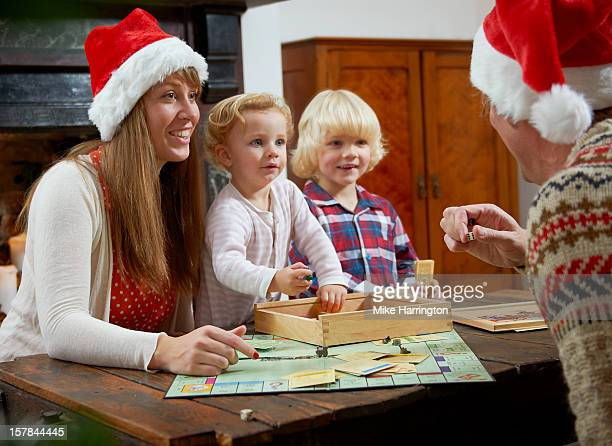 Family with board game, parents in Christmas hats.