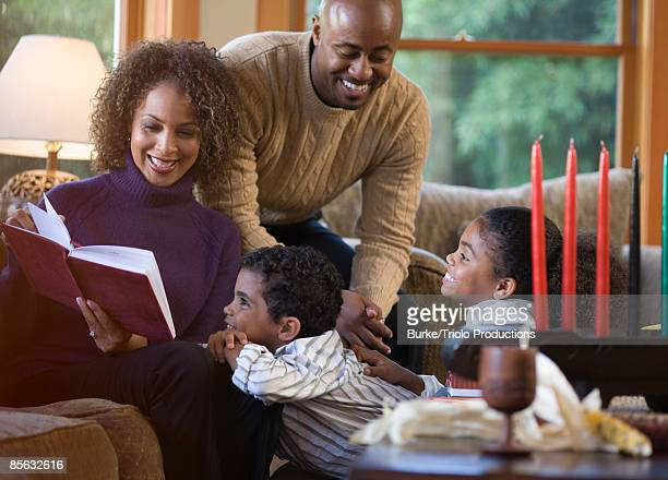 Family with book and Kwanzaa candles
