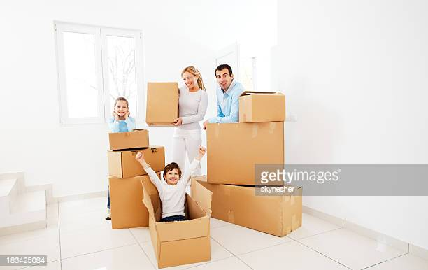 Family with boxes are moving into new home.