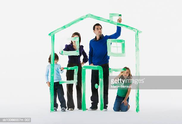 Family with boy and girl (6-9) painting house outline, on white background