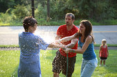 Family with boy (10-11) having water fight, outdoors