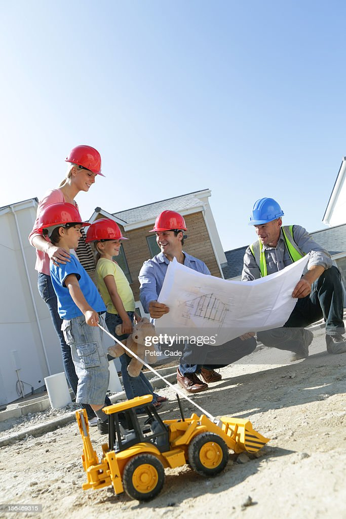 Family with builder looking at new house plans : Stock Photo