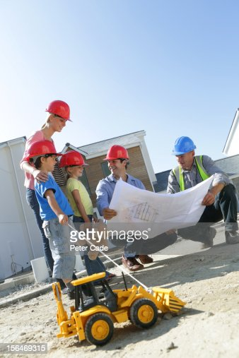 Family with builder looking at new house plans : ストックフォト
