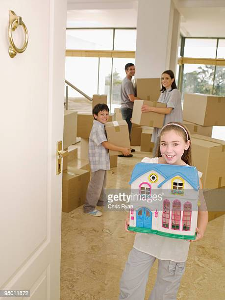 Family with cardboard boxes and dollhouse