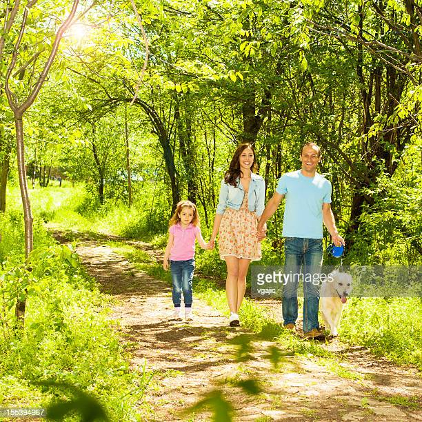 Family With Child and dog Walking Outdoors.