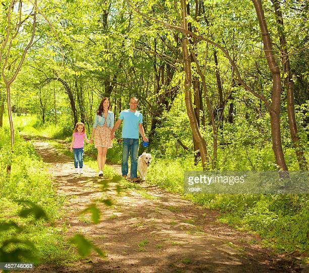 Familie mit Kind und Hund gehen im Freien.