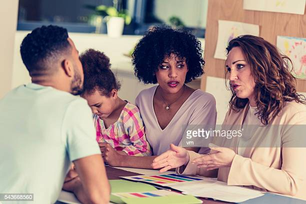 Family with child talking to the girls teacher