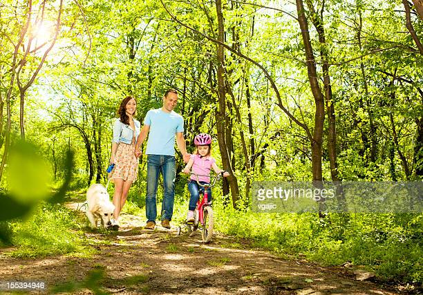 Family With Child Walking and cycling in a forest.