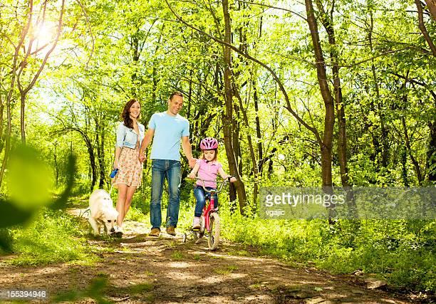 Familie mit Kind, Walking und Radsport in einem Wald.