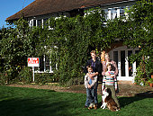 Family with children (7-9) and dog in front of house, portrait