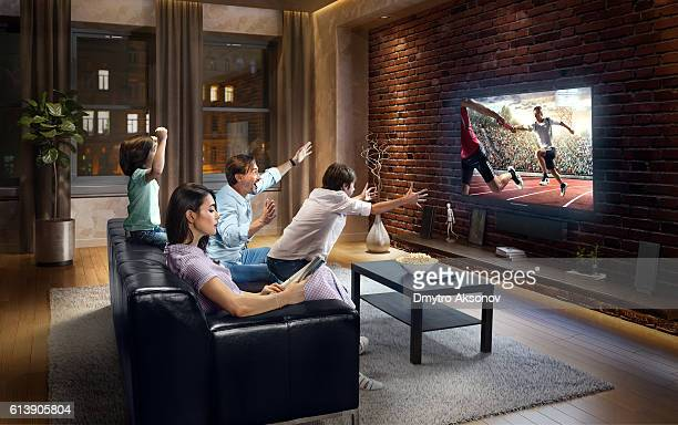 Family with children cheering and watching Relay race on TV