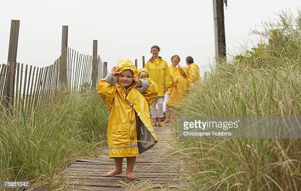 Family with children (2-3) in yellow raincoats walking along boardwalk, full length