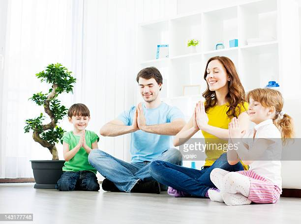 Famille avec enfants en pratiquant le yoga à la maison.