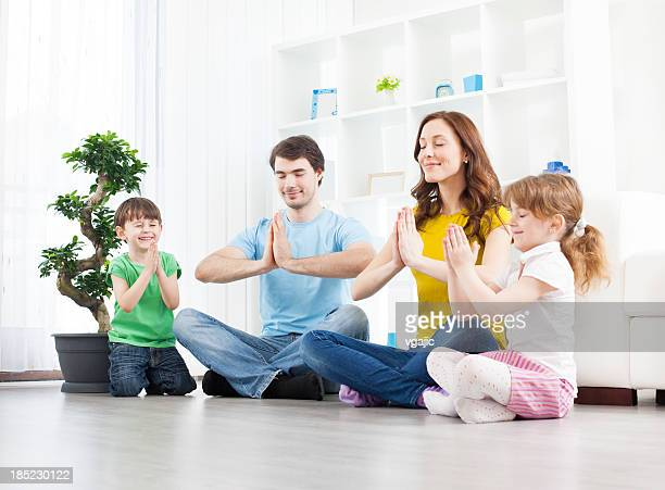 Family with children practicing yoga at home.