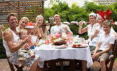 Family with children (1-12 years) raising glasses, wearing Christmas hats at outdoor table