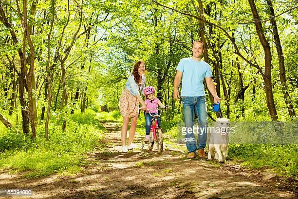 Familie mit Kindern zu Fuß oder mit dem Fahrrad in einem Wald.