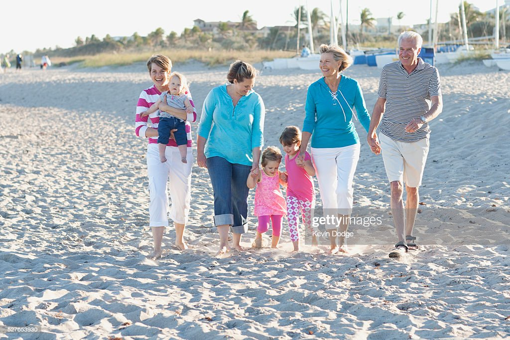 Family with children (12-23 months, 2-3, 4-5 years) walking on beach