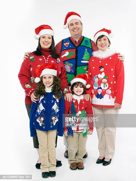 Family with children (4-7) wearing Christmas sweaters and santa hats, portrait