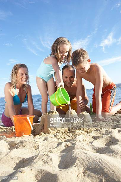 Family with daughter (7-9) and son (11-13) building sandcastles on beach