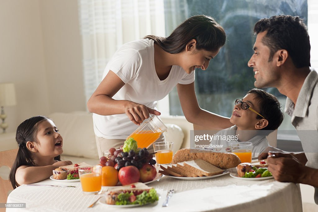 Family with daughter and son (6-7) having breakfast